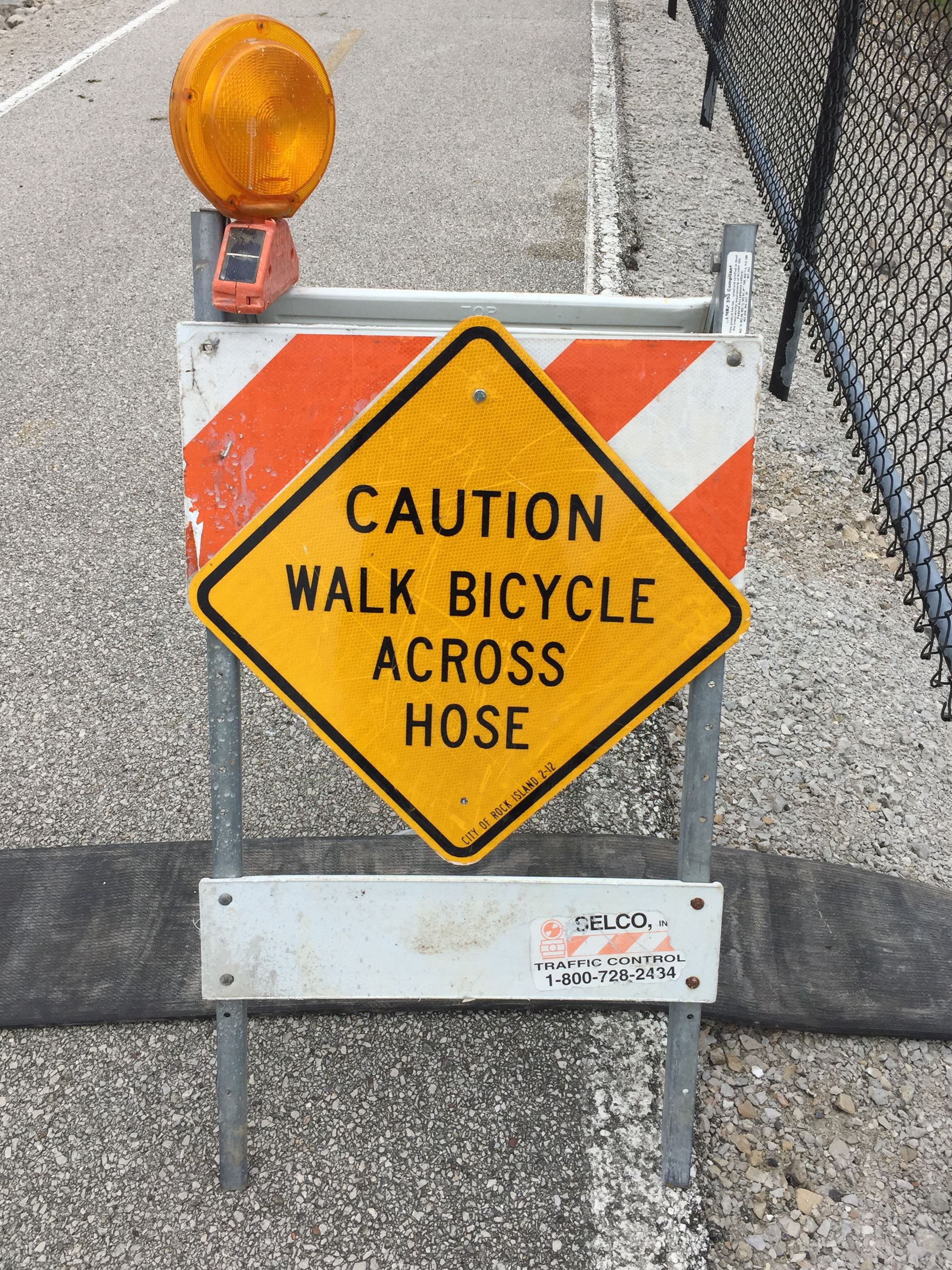 Caution Walk Bicycle Across Hose sign