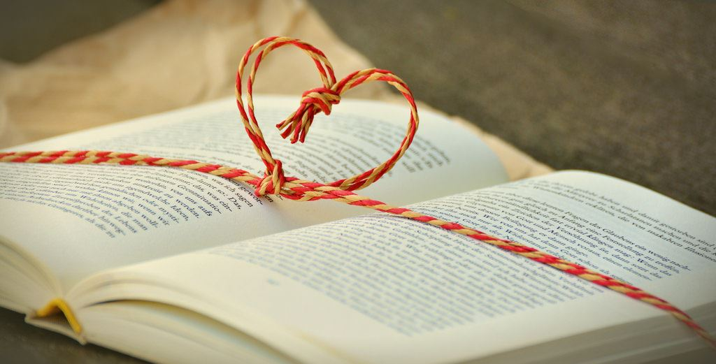 photo of a book with a heart tied out of string above