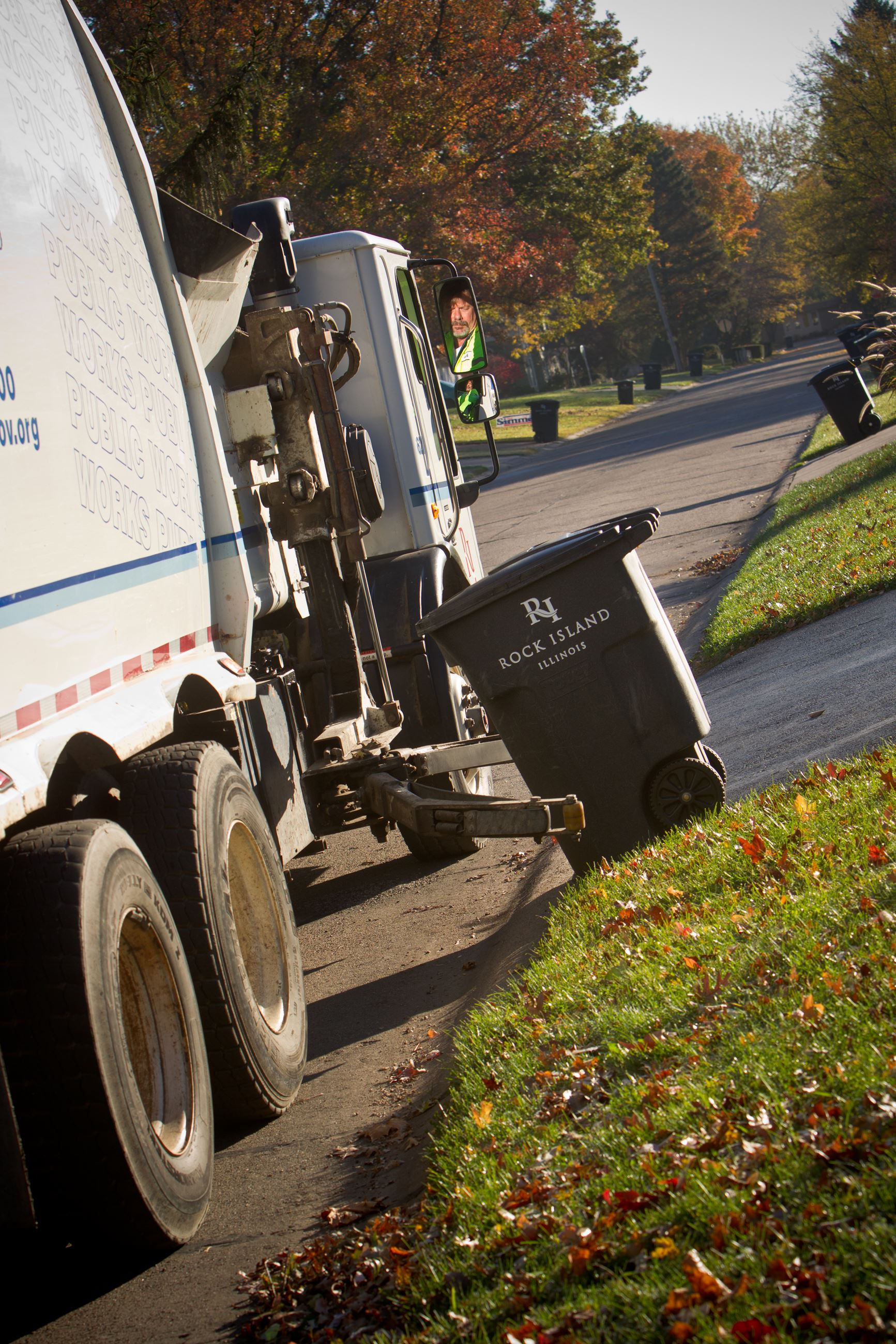 Refuse truck and cart in neighborhood